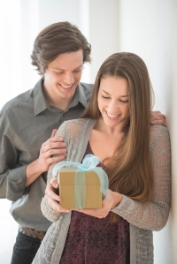 Man Giving Birthday Present To Woman At Home