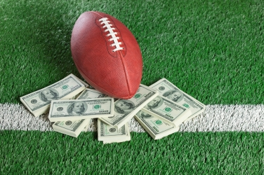 NFL football sitting with piles of dollars on AstroTurf