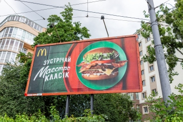 Closeup of Mcdonalds advertisement ad banner sign in Ukrainian city by street buildings, cyrillic and burger picture